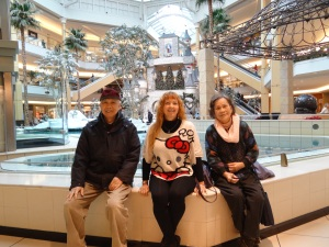 Papa, Mama, and Me sitting in front of one of the holiday displays in the mall